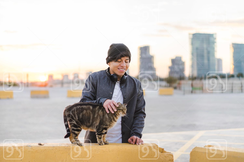 Asian man stroking a cat