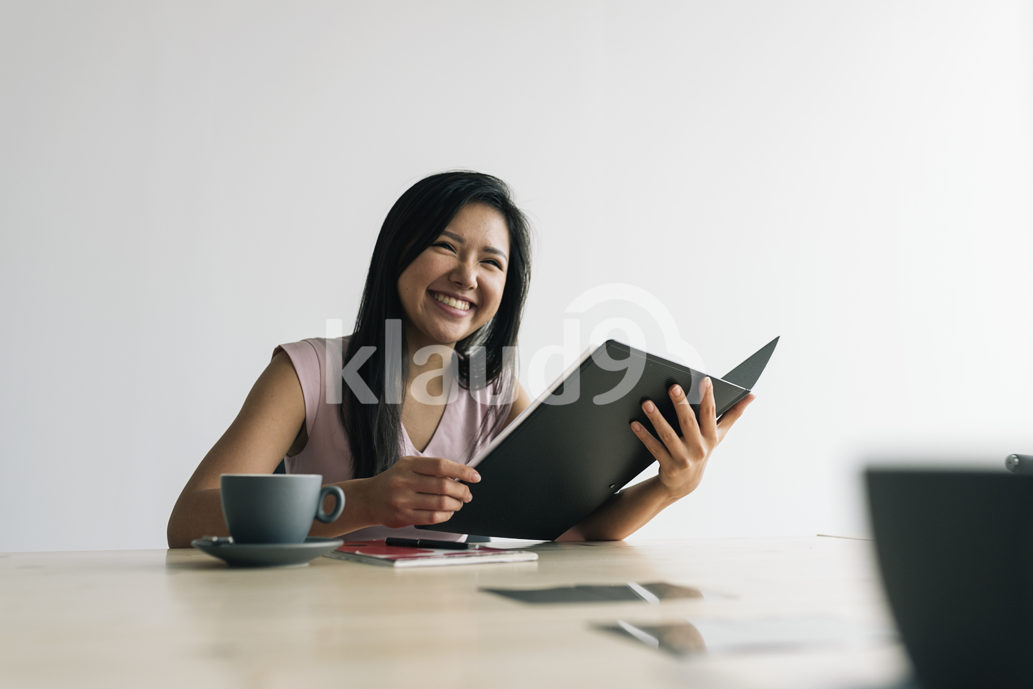 Happy Asian woman smiling holding documents