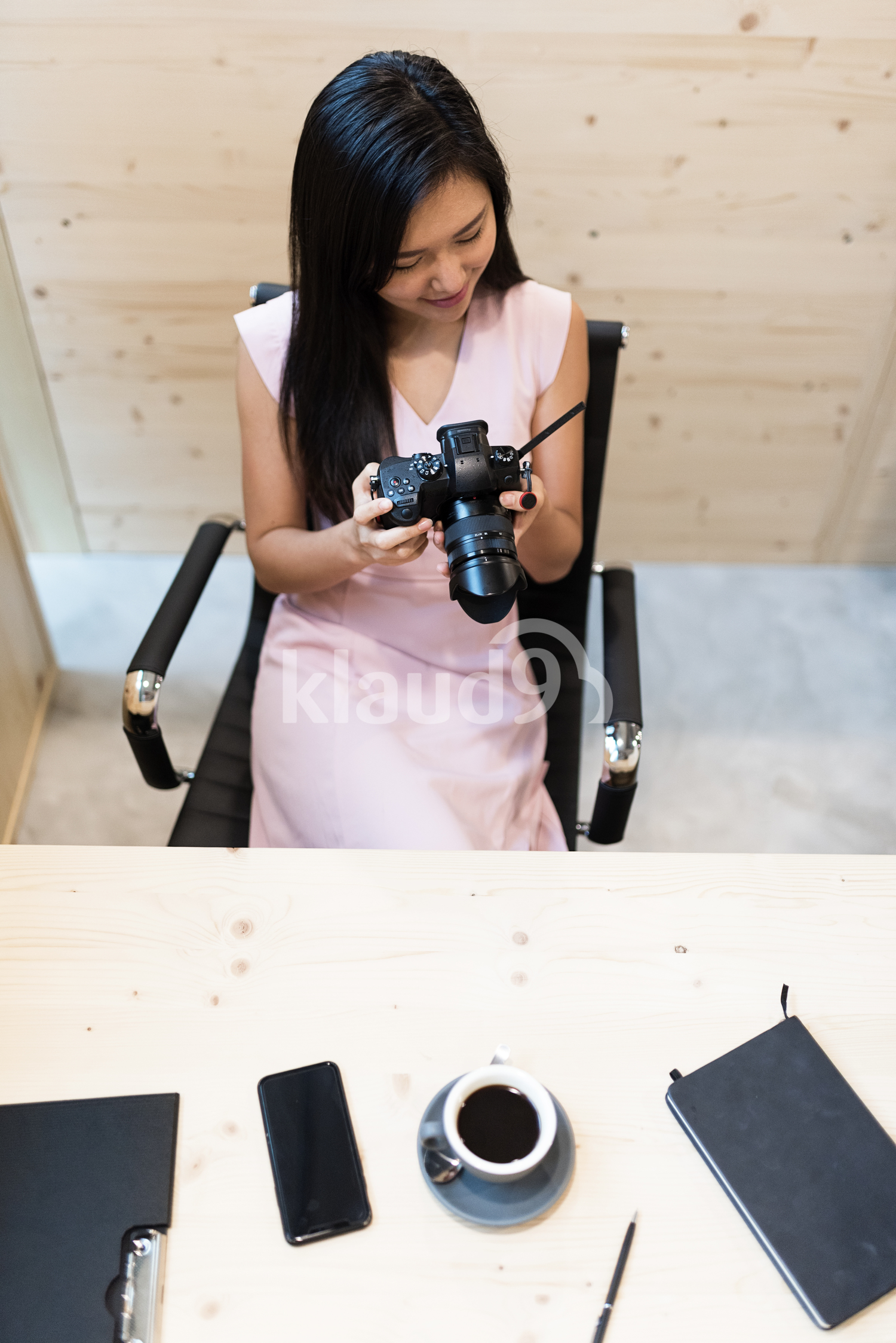 Pretty woman at her work space holding a camera