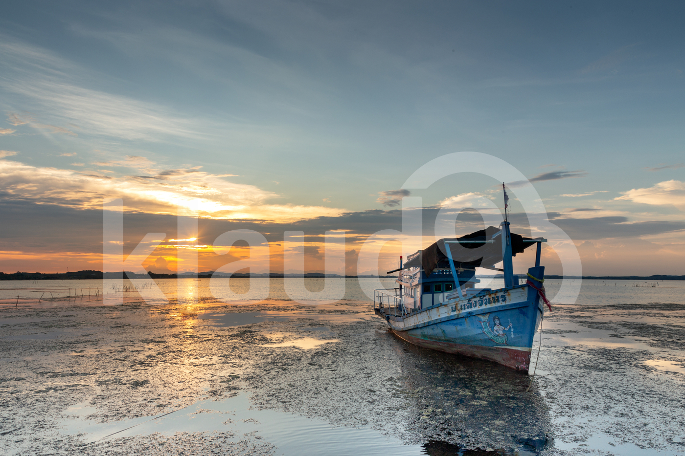 Abandoned fishing boat by the lake at sunset