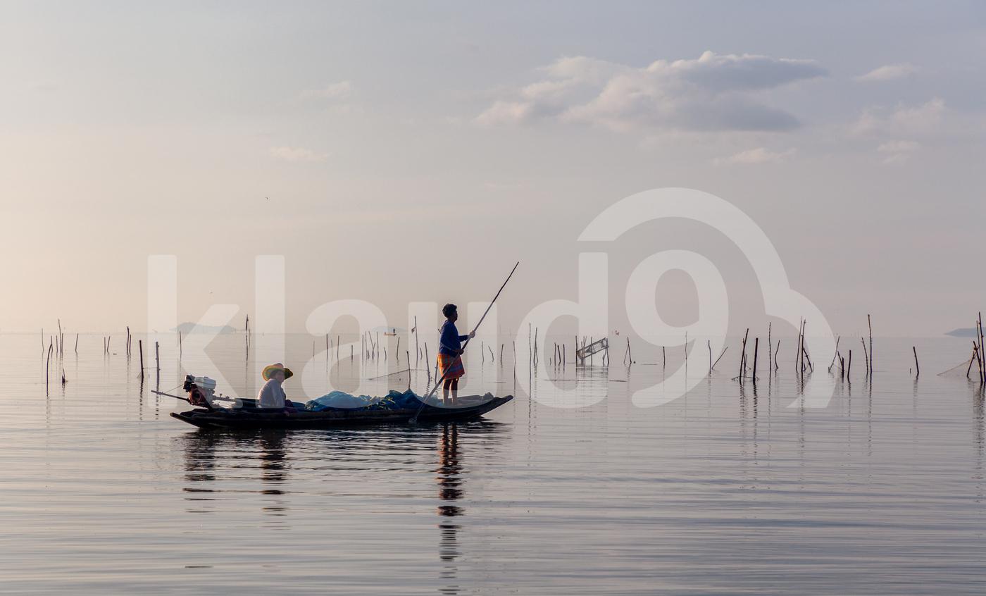 Fishermen on the boat at sunrise