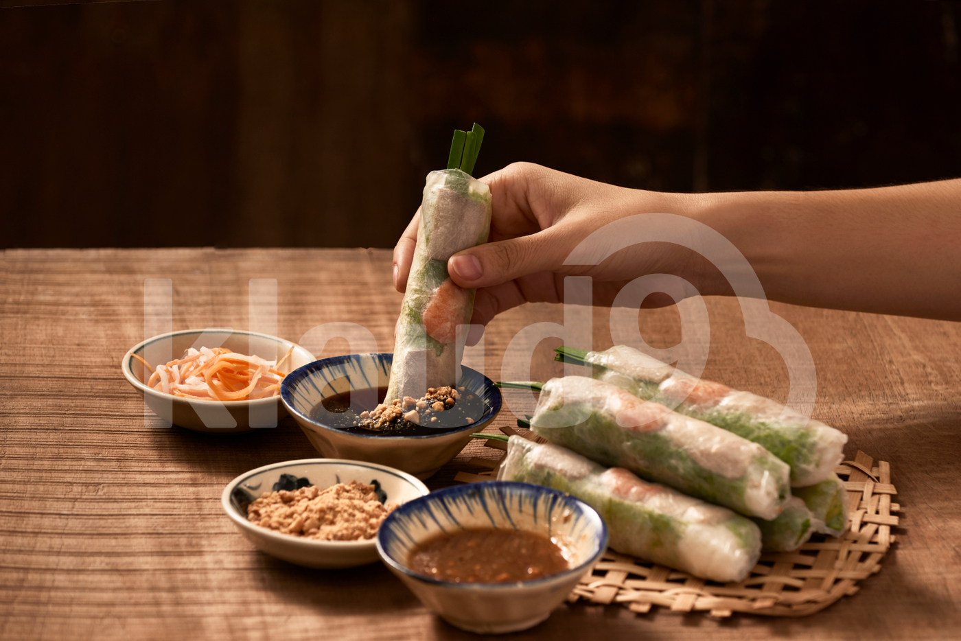 Young woman's hands eating healthy spring roll dipped in a soya sauce. Selective focus.