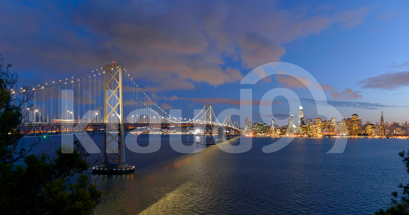 San Francisco Bay Bridge And Evening Skyline on a cloudy day.