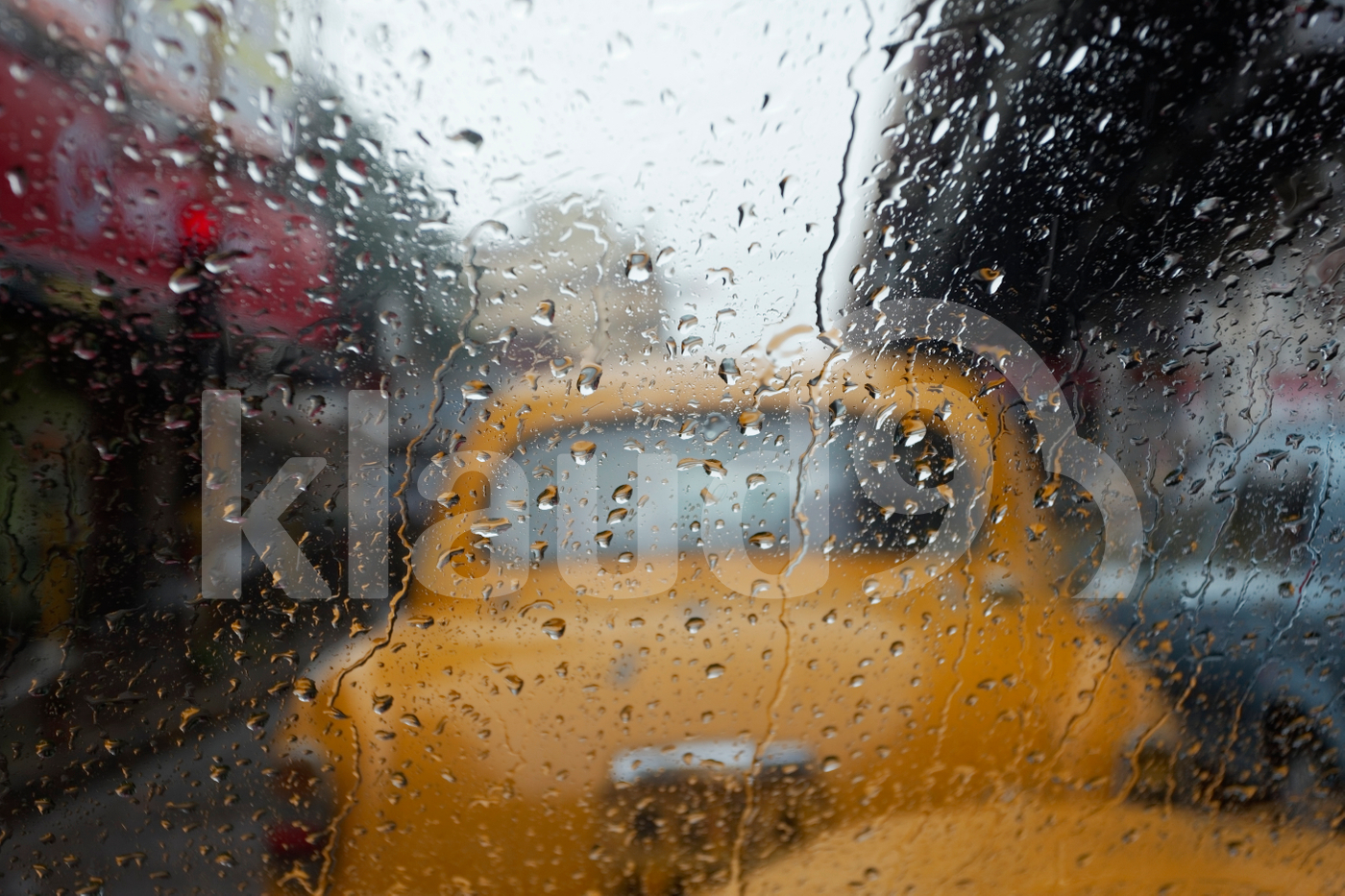 Rain drops on wind screen of a car showing yellow cabs Kolkata, India.