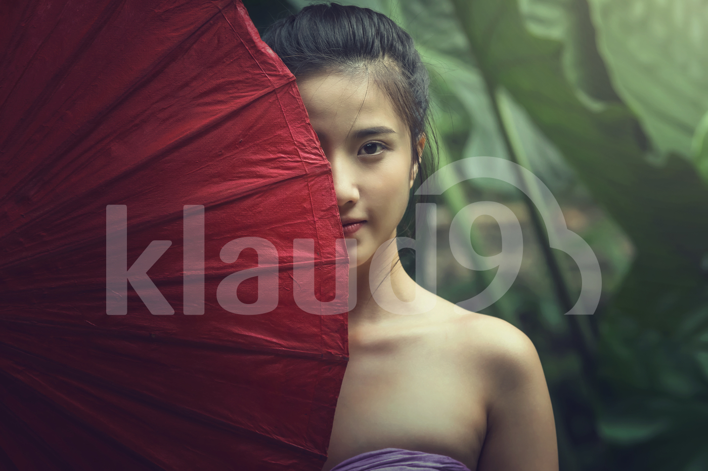 Closeup Portrait of beautiful Village women standing with red color traditional umbrell in forest, countryside and Folkways concept