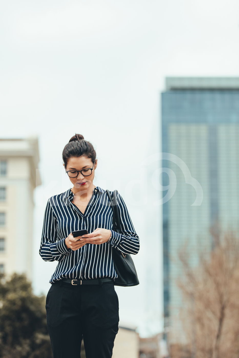 Businesswoman walking outdoors and using cellphone