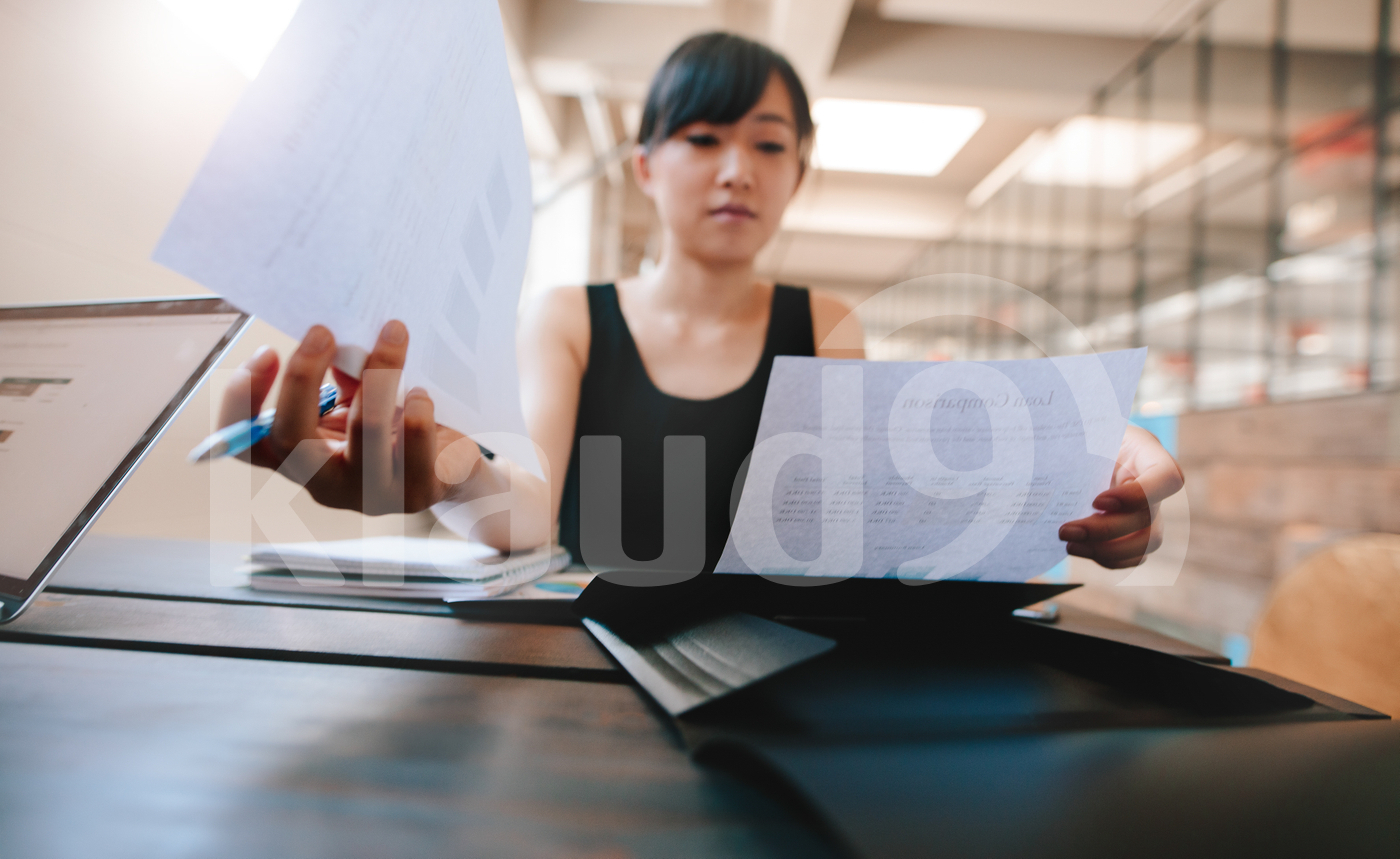 Businesswoman going through documents at her desk
