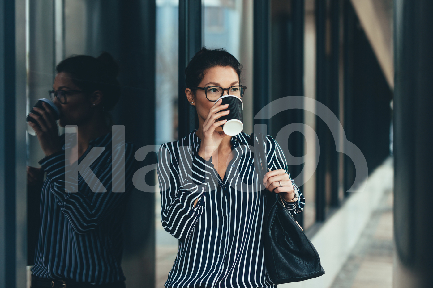 Businesswoman outside office building drinking coffee