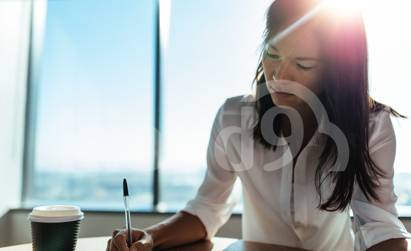 Closeup of a businesswoman sitting at coffee table doing office work.
