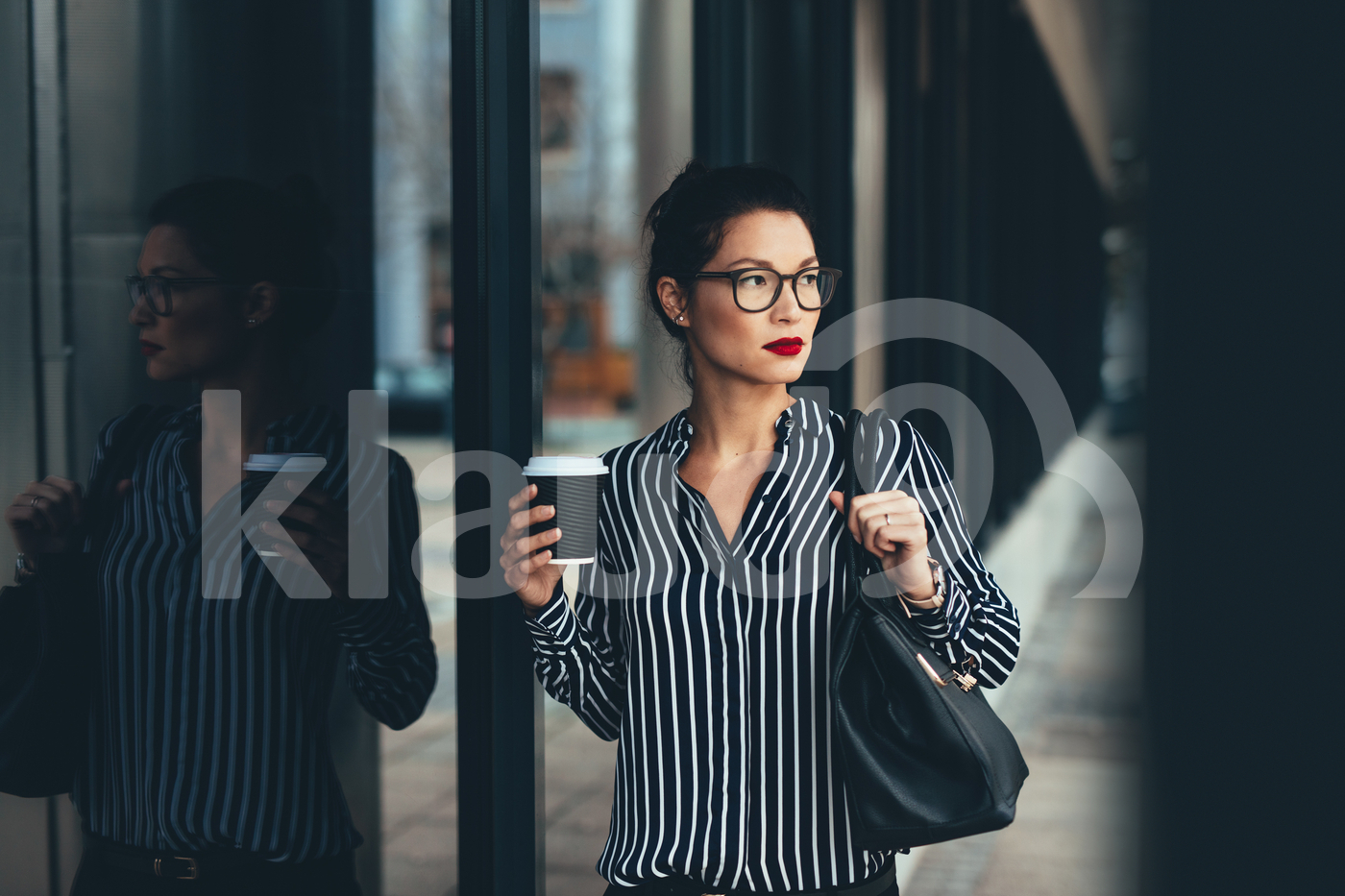 Businesswoman outside office building with a coffee