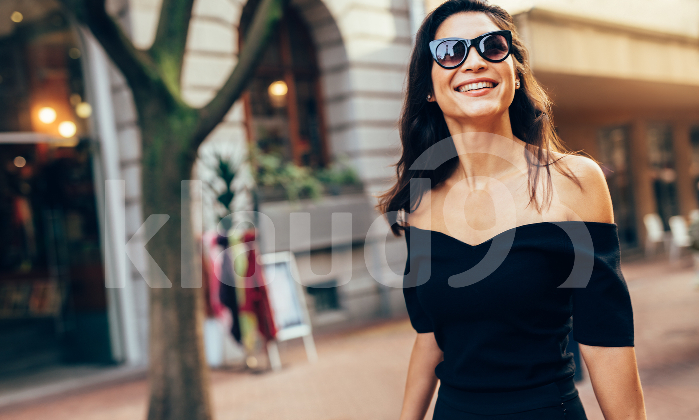 Smiling woman walking along the road in city