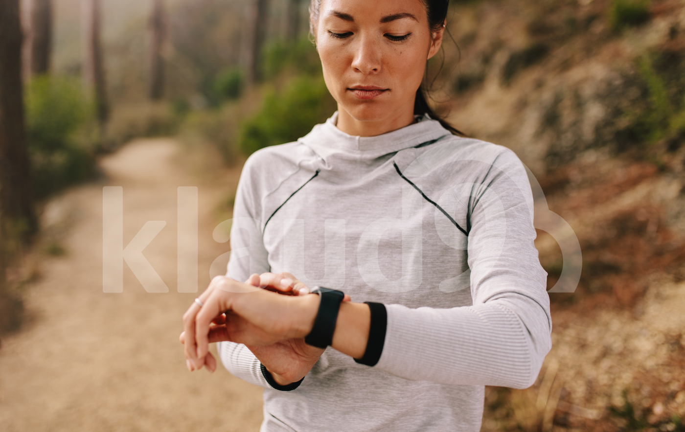 Young fitness woman runner checking time on smart watch.