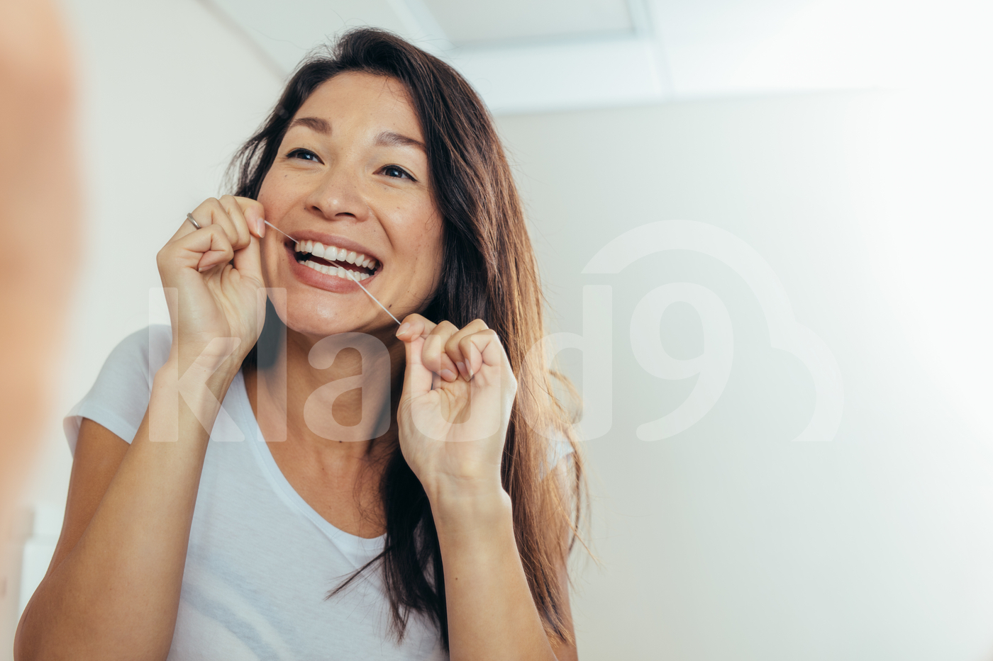 Reflection of woman using dental floss