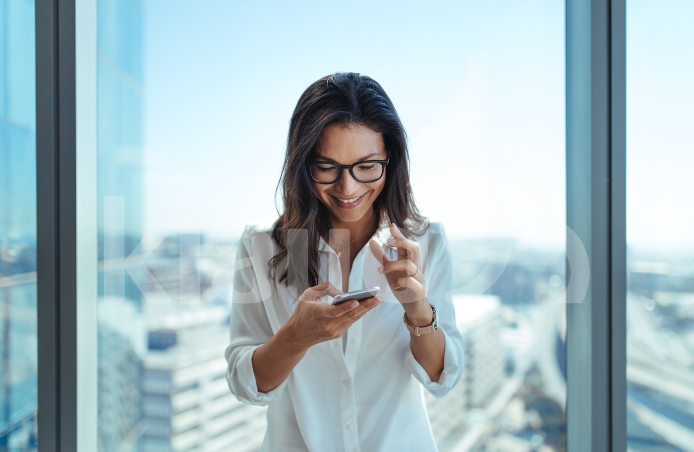 Happy businesswoman using her mobile phone at office.
