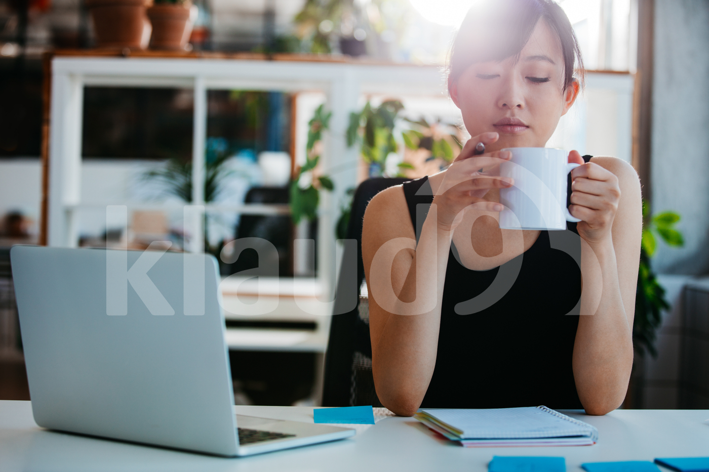Relaxed young woman having coffee at her desk