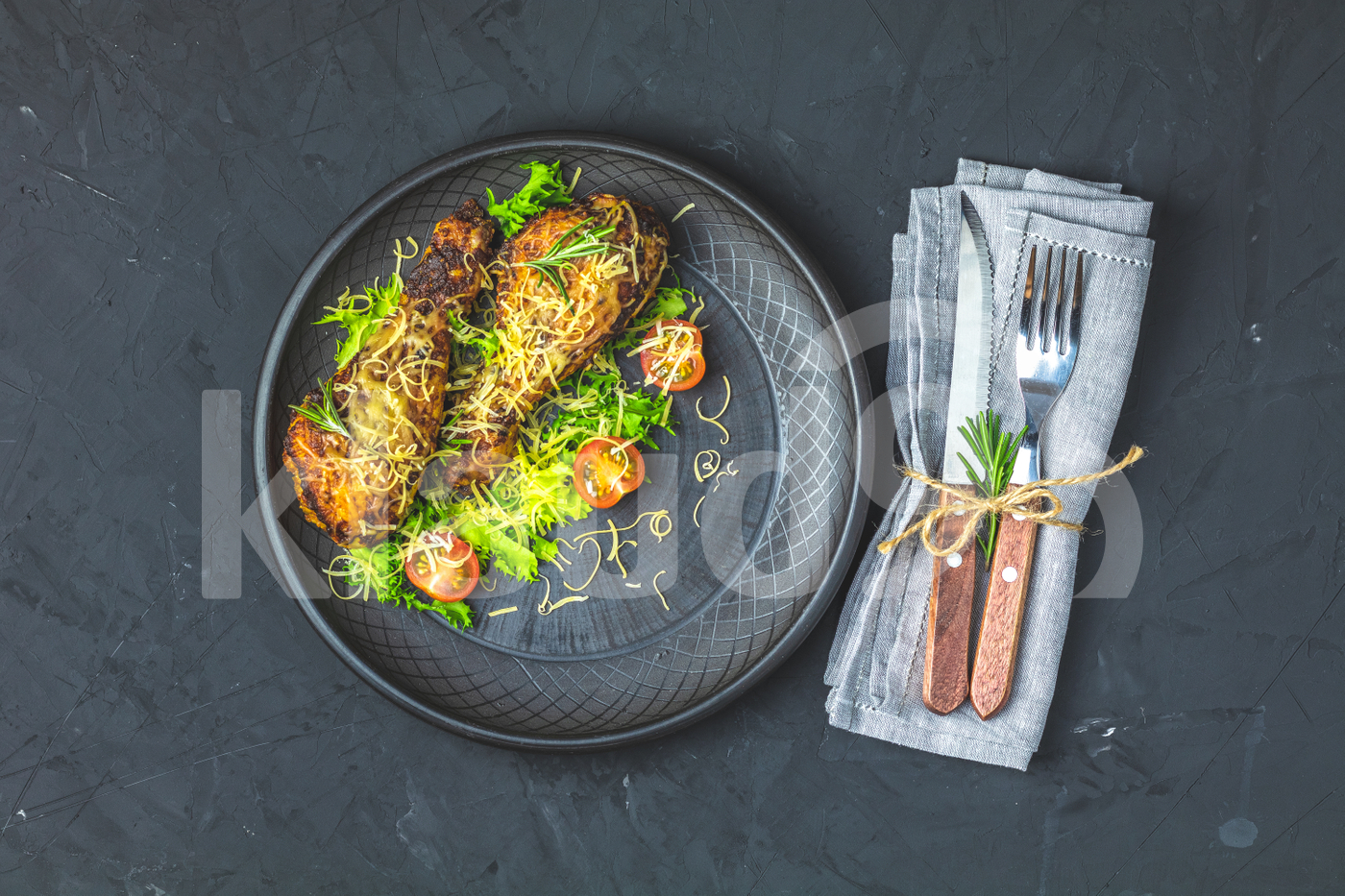Baked chicken drumstick in a black ceramic plate with orange and rosemary