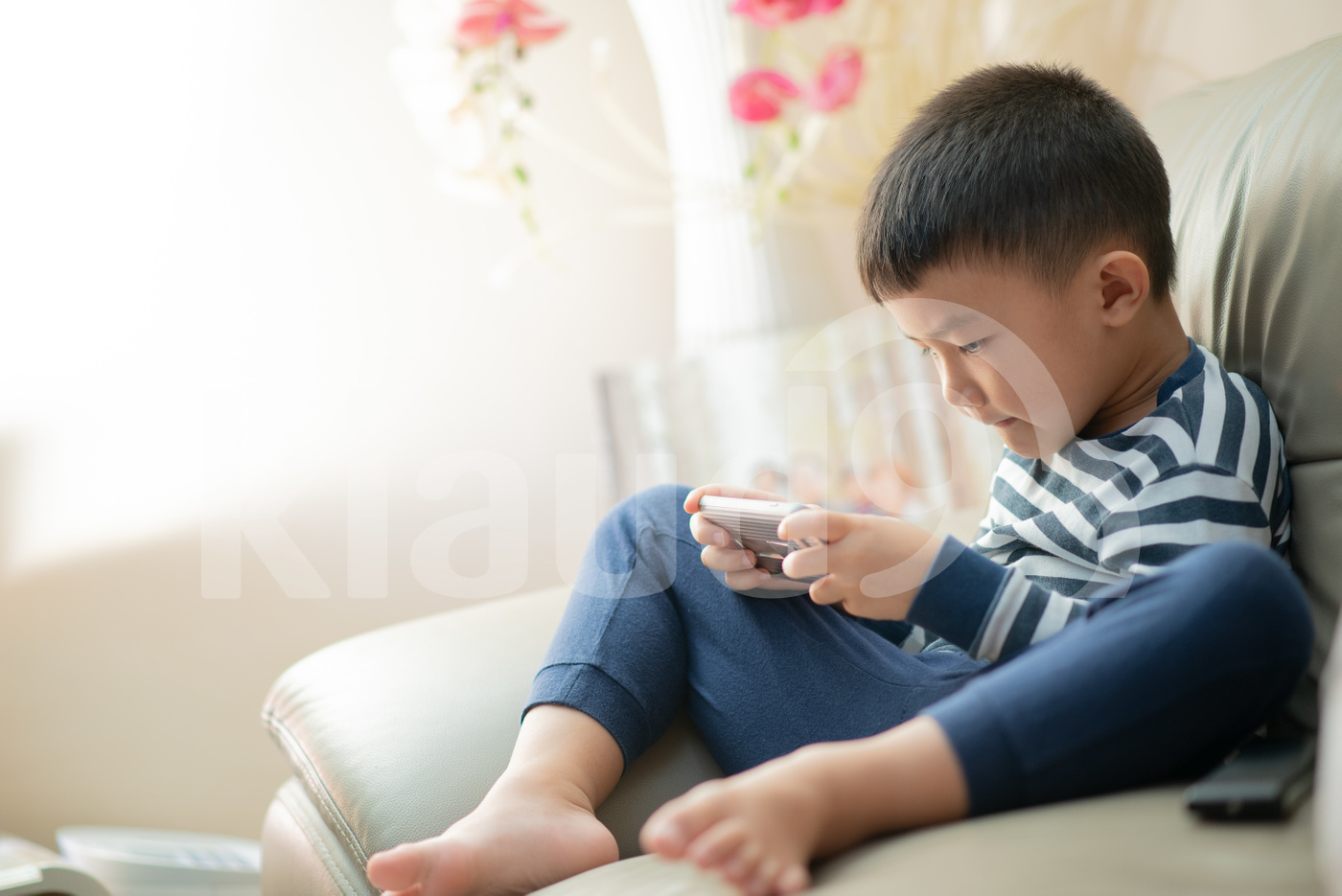 Asian child at home during lockdown, playing with phone