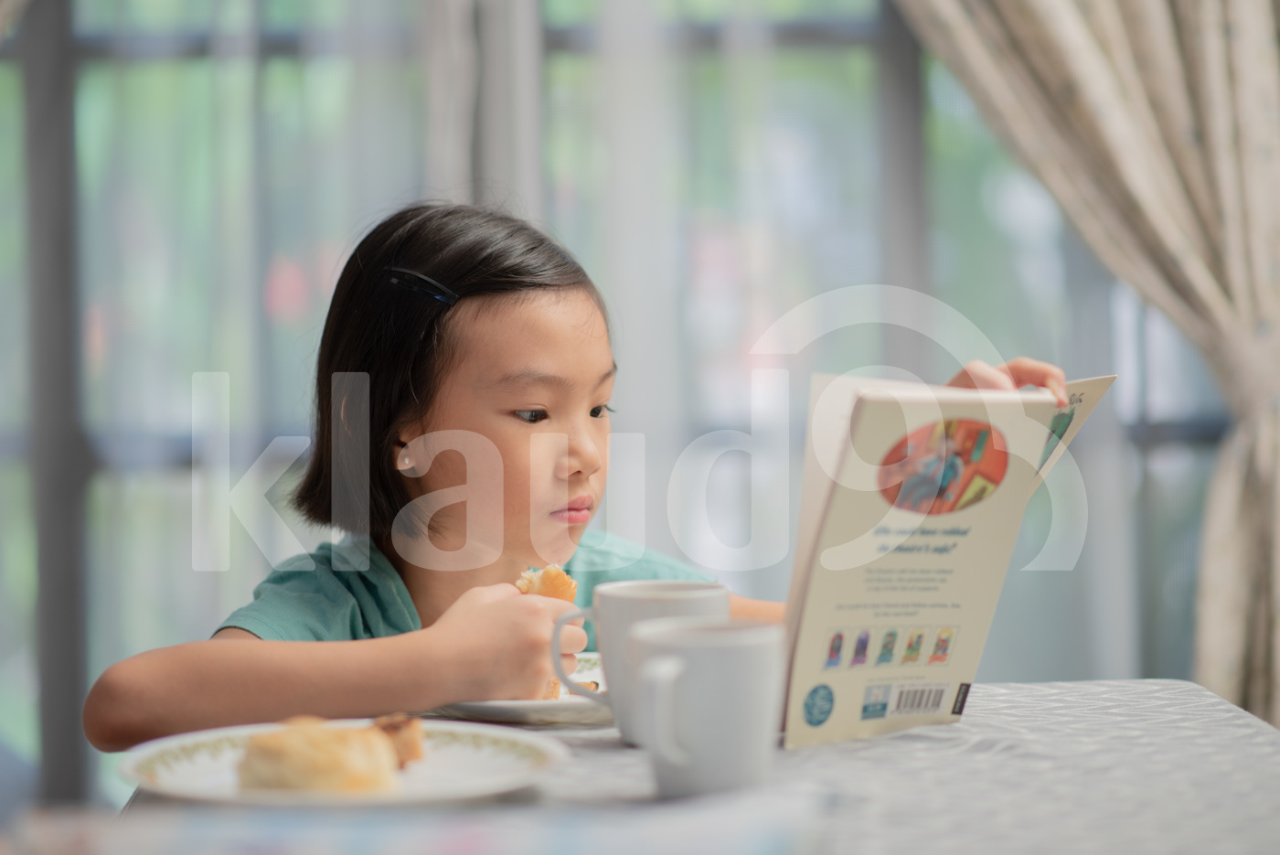 Asian Chinese child reading story book during breakfast