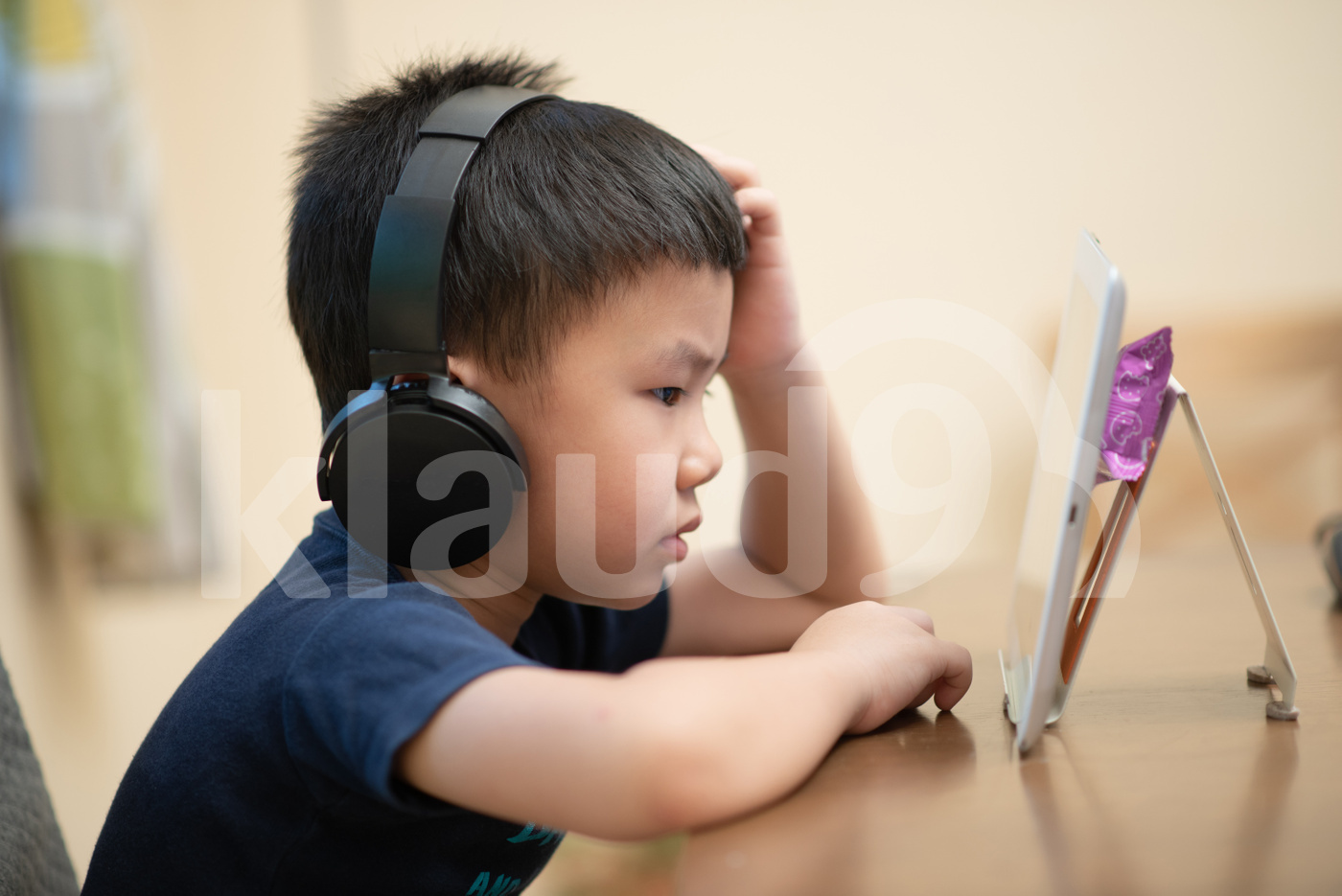 Asian child doing online learning or e-learning at home
