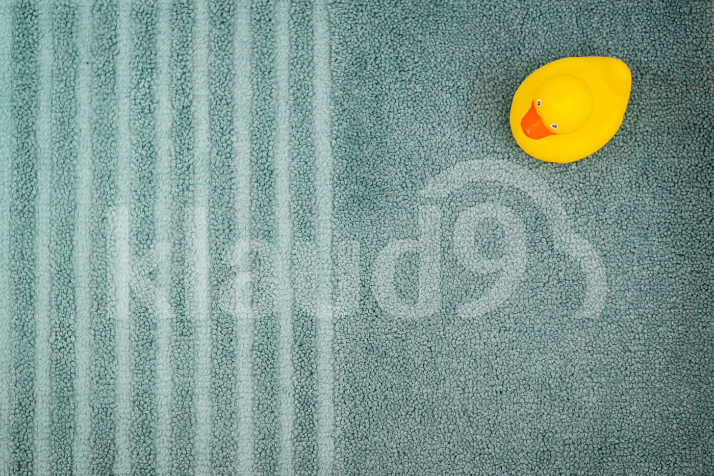 Yellow rubber duck over the bathmat in the bathroom