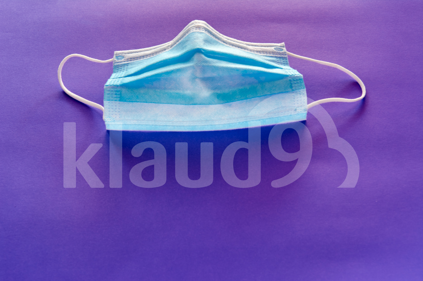 Blue medical face mask to avoid contagious diseases pattern on purple background