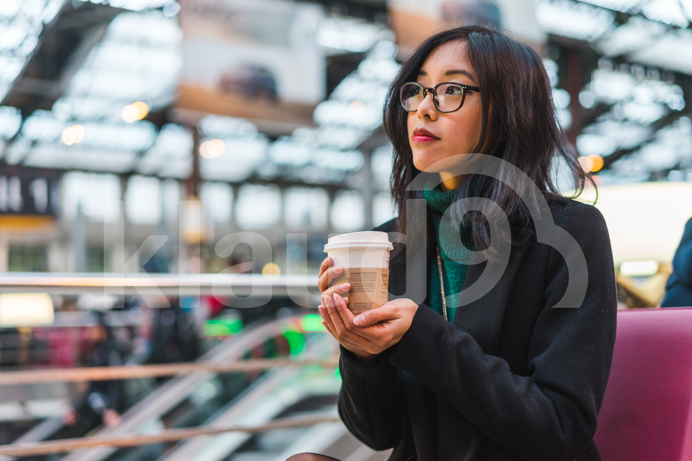 Young adult Asian woman sitting in a train station and holding coffee cup