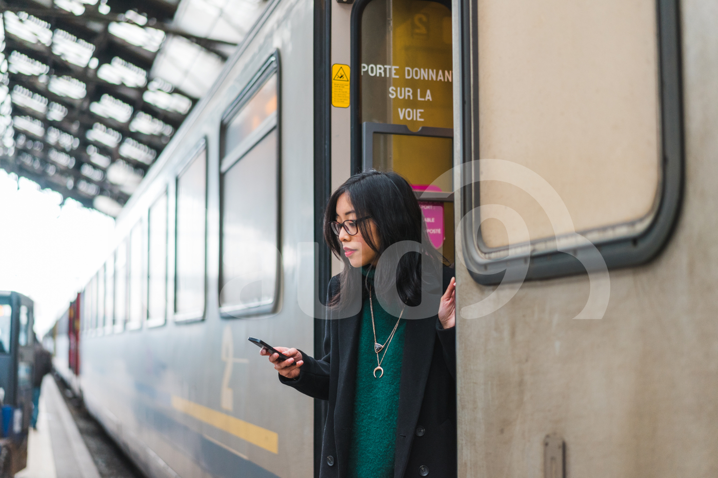 Young Asian woman stepping off a train looking at her mobile