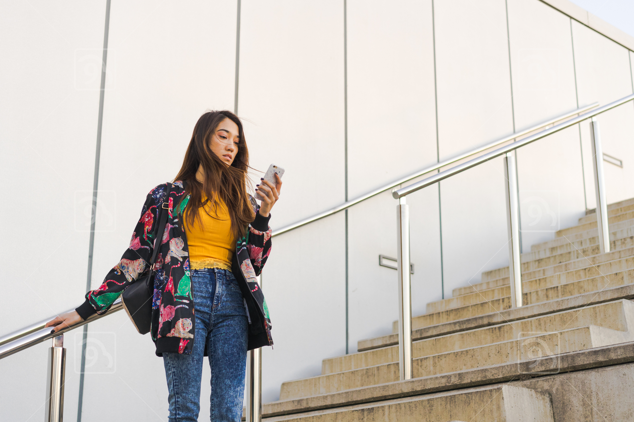Young adult woman standing outdoors using smartphone