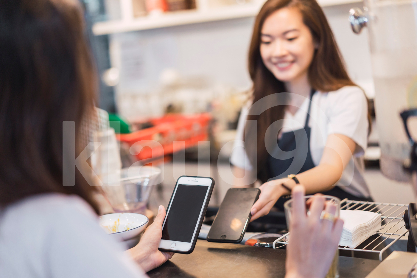 Female customer making payment transaction with smartphone