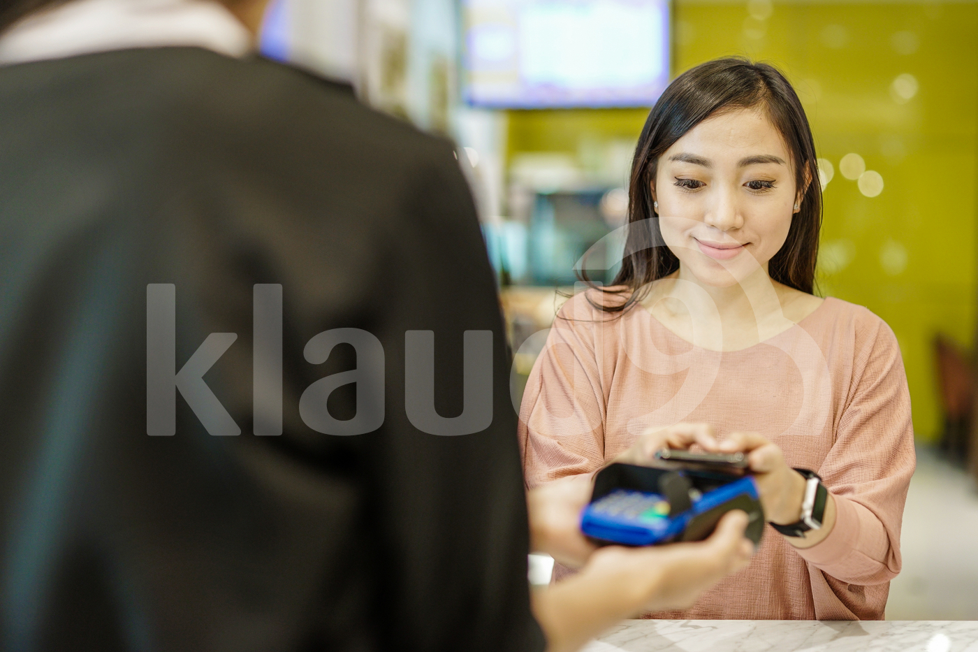 Smiling woman  at restaurant making e-wallet payment