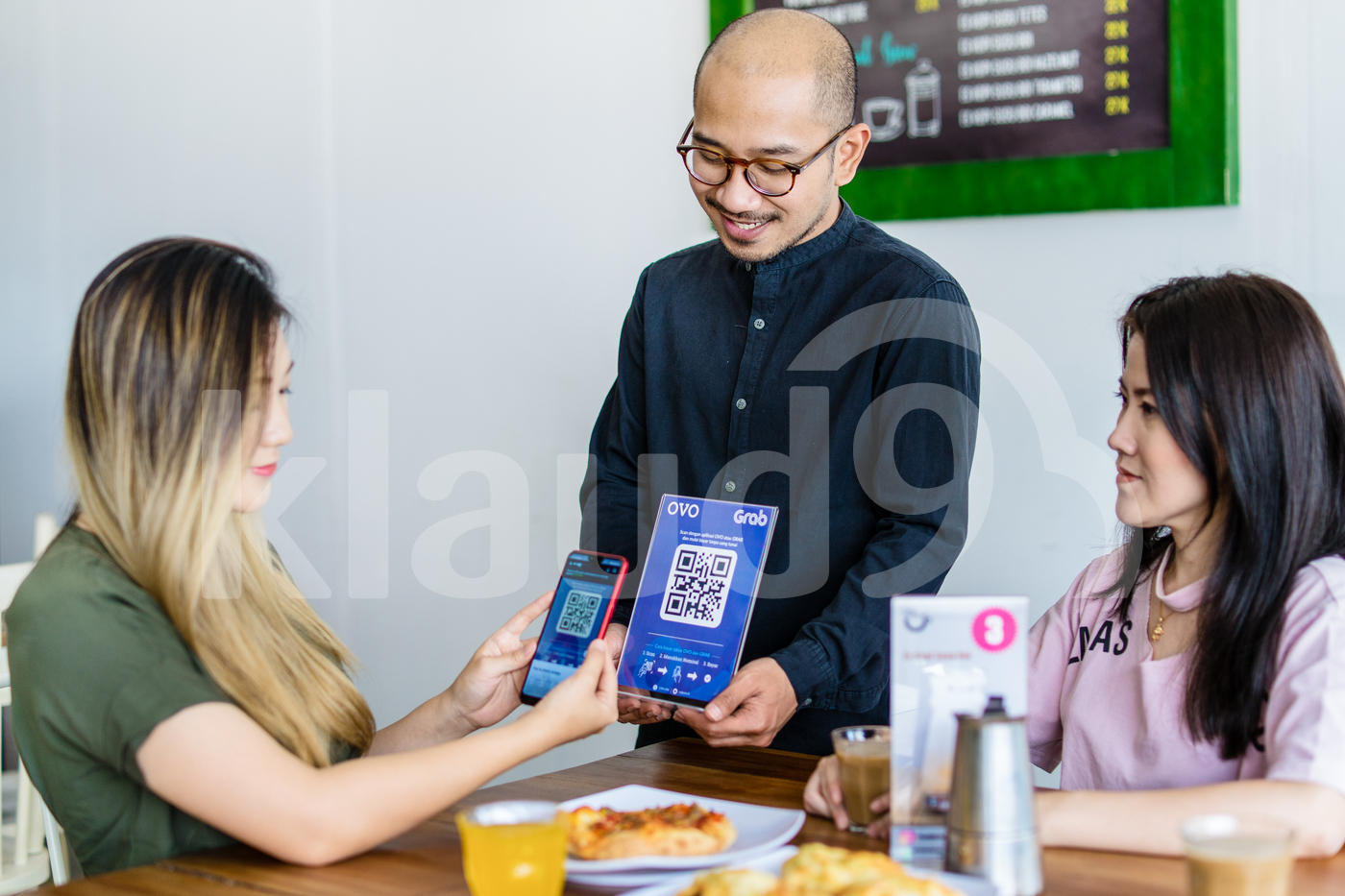Asian Woman scanning QR code with smartphone to make payment