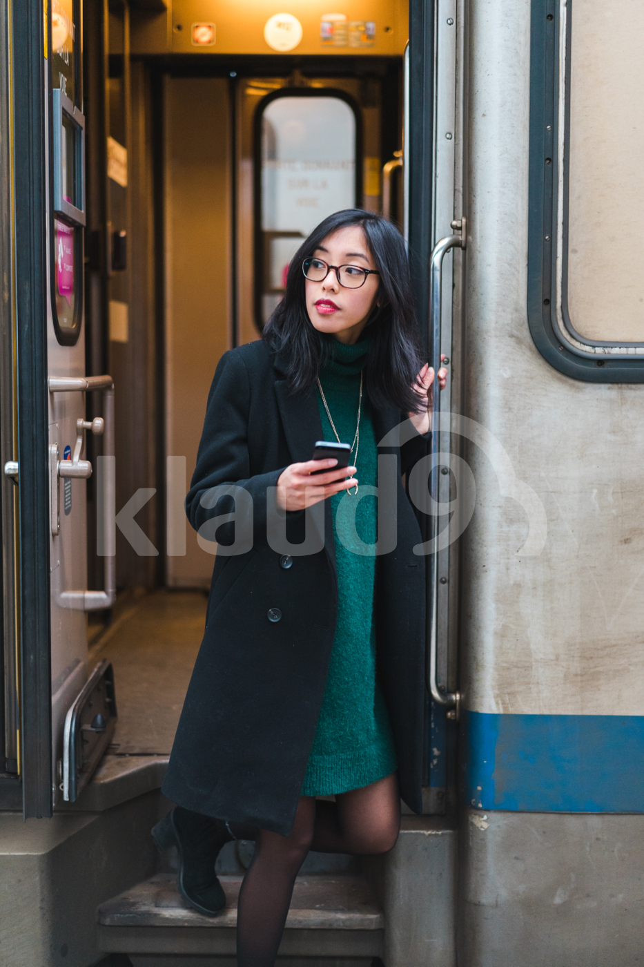 Young Asian woman stepping off a train holding her mobile