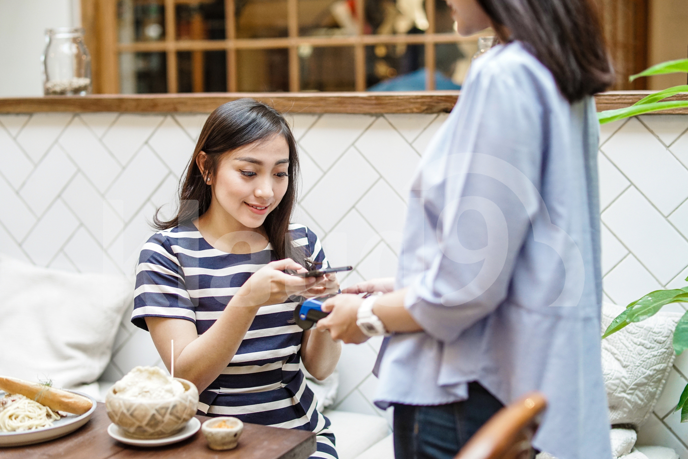 Young Asian woman with smartphone using contactless payment at restaurant