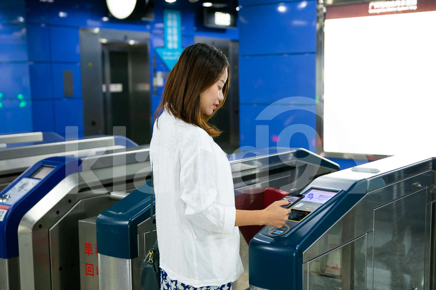 Young Asian woman making payment with mobile at the train station