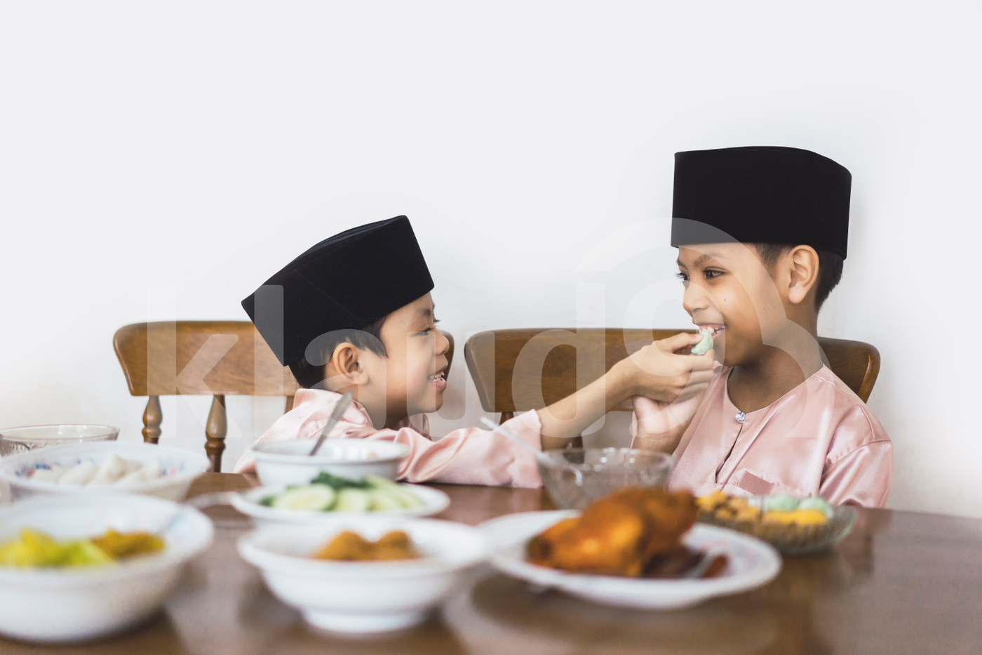 Muslim children feeding each other
