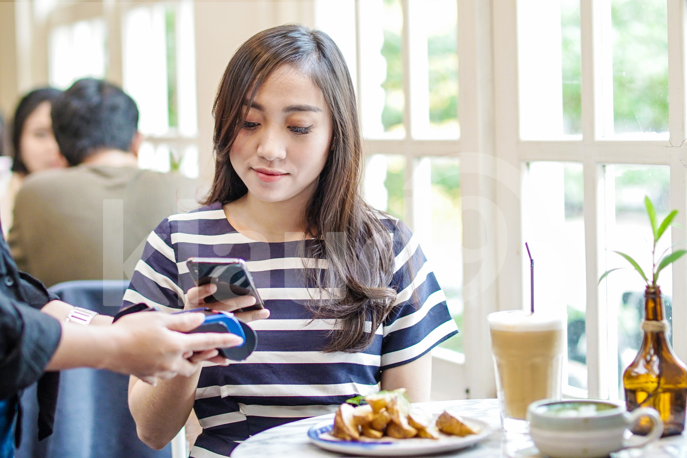 Asian woman making payment with mobile in a coffee shop