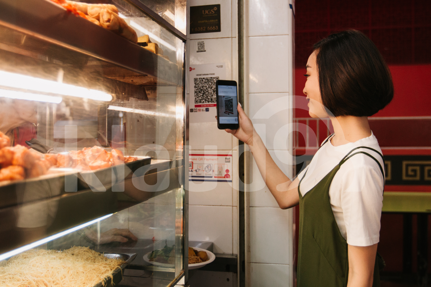 Young adult Asian woman scanning QR code in a food court