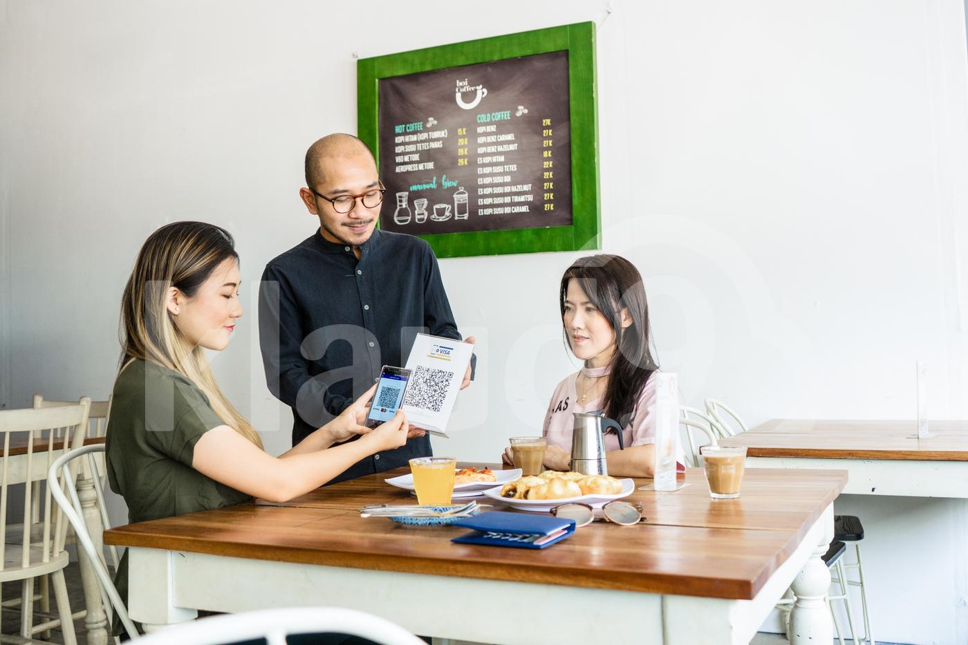 Asian woman scanning QR code in a  restaurant