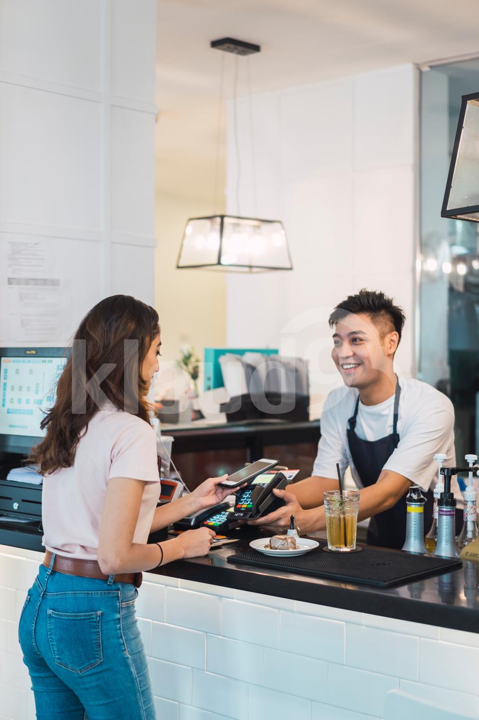 Asian Woman paying bill through smartphone