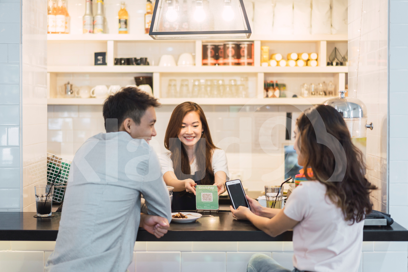 Couple at coffee shop making e-wallet payment