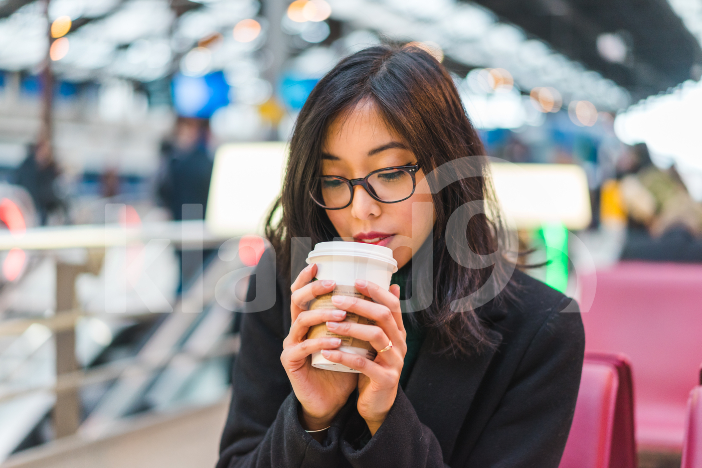 Young adult Asian woman drinking a coffee