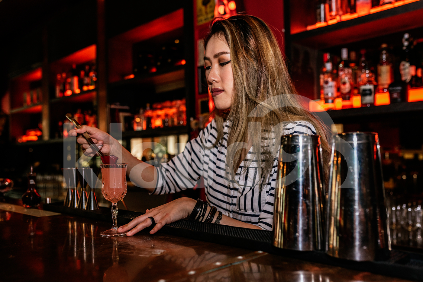 Female Asian bartender preparing a drink