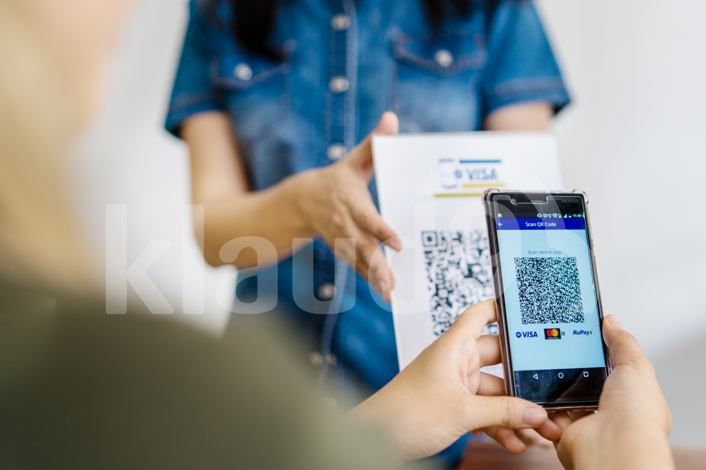 Woman scanning QR code in restaurant to make payment