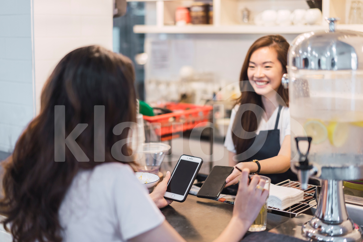 Young Asian woman making payment through smartphone at restaurant