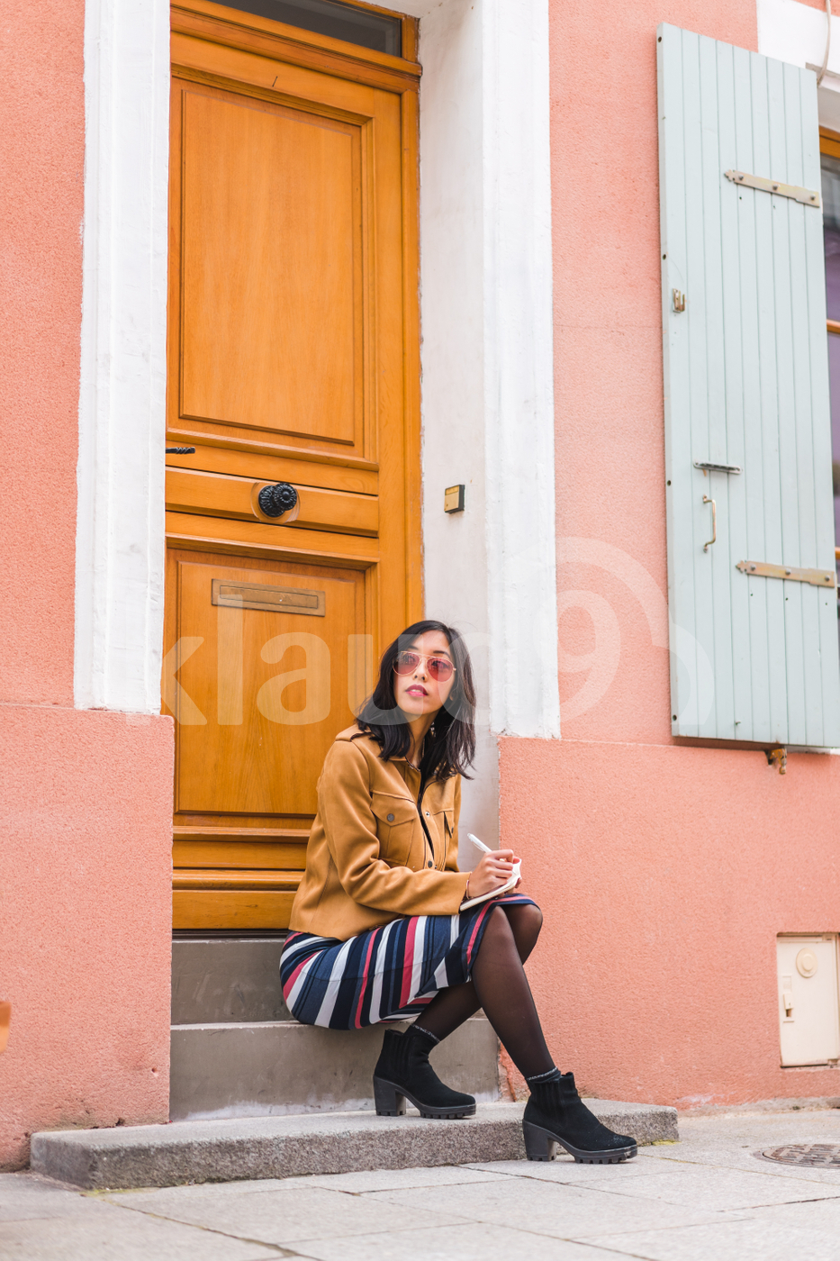 Young adult Asian woman  sitting in front of a house