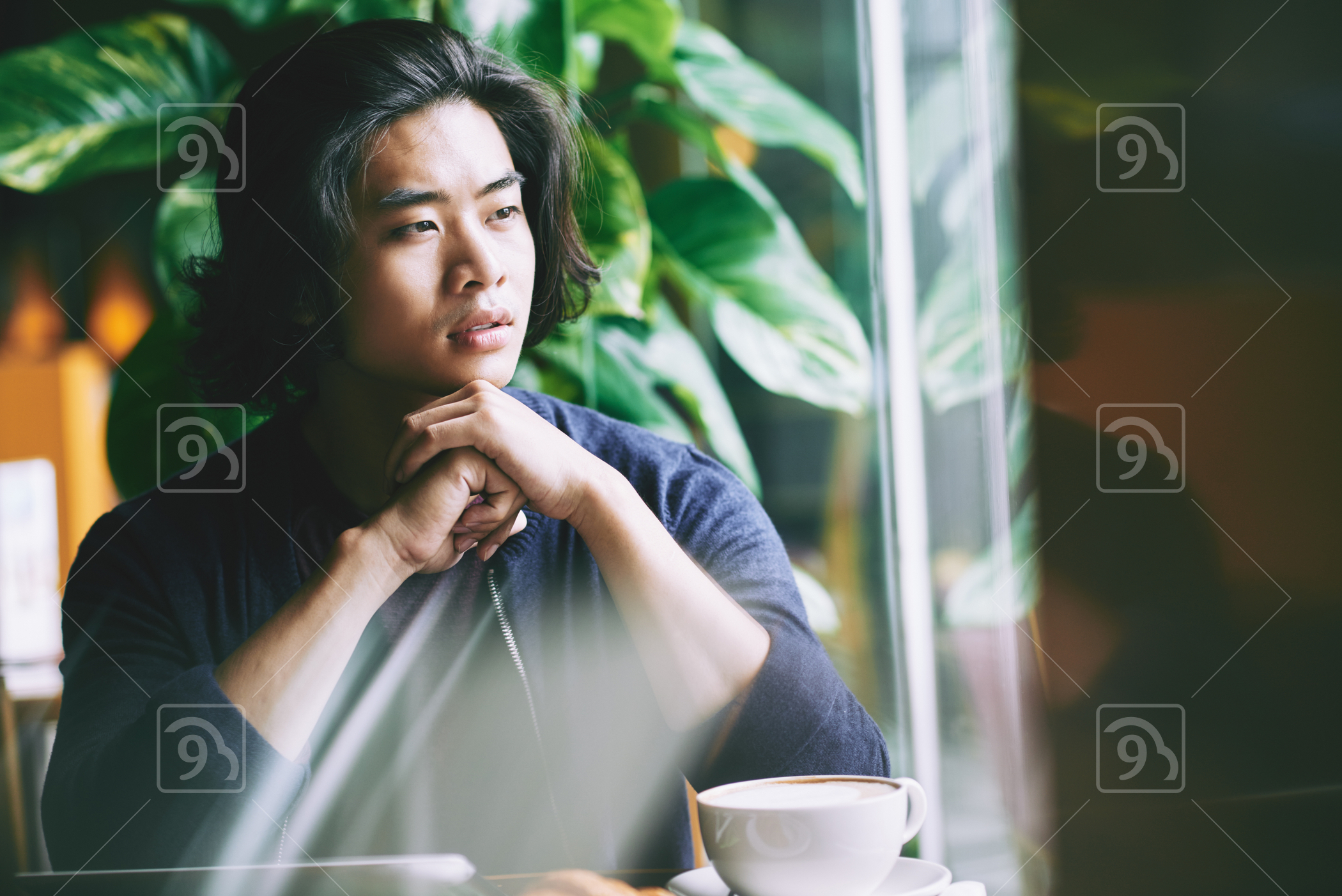 Portrait of pensive handsome man sitting in cafe