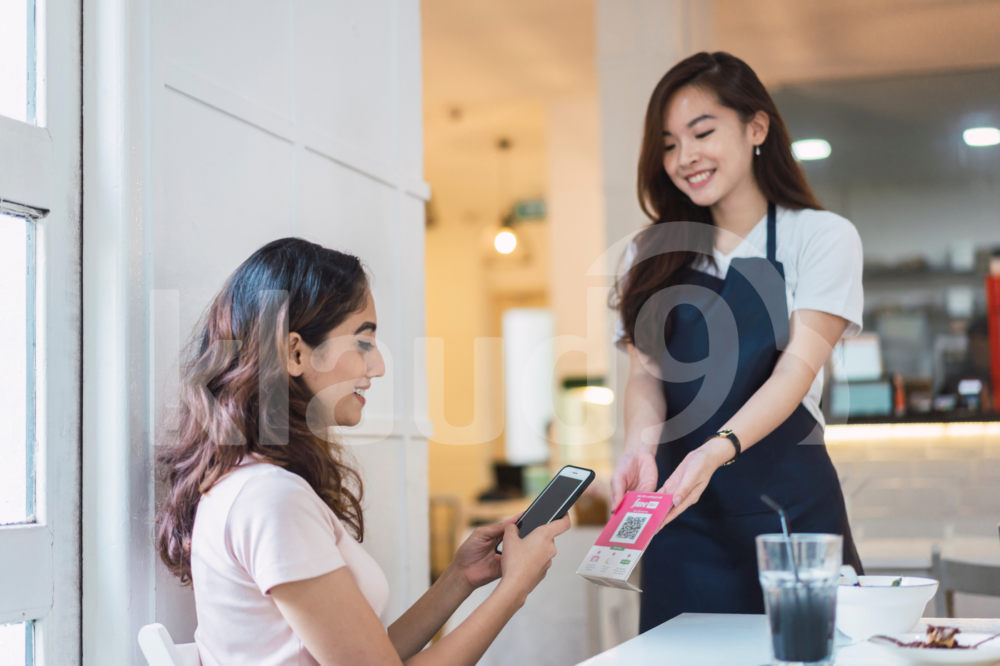 Asian client making payment with mobile at table