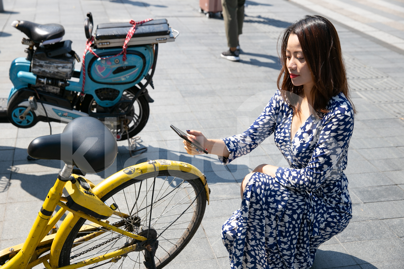 Asian woman scanning QR code to make payment for a bicycle