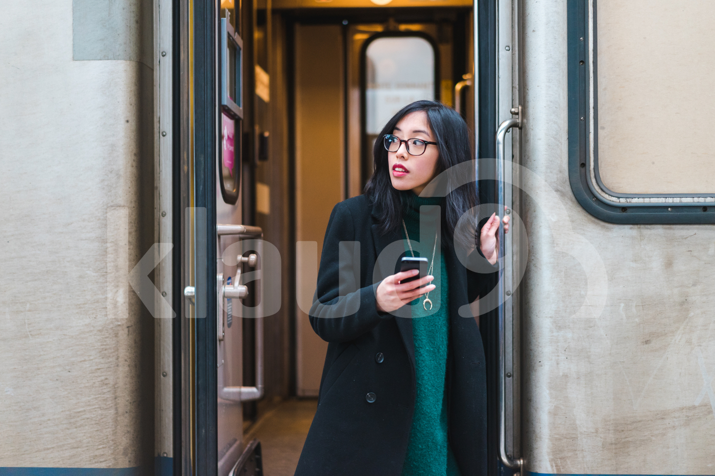 Asian woman stepping off a train holding her mobile