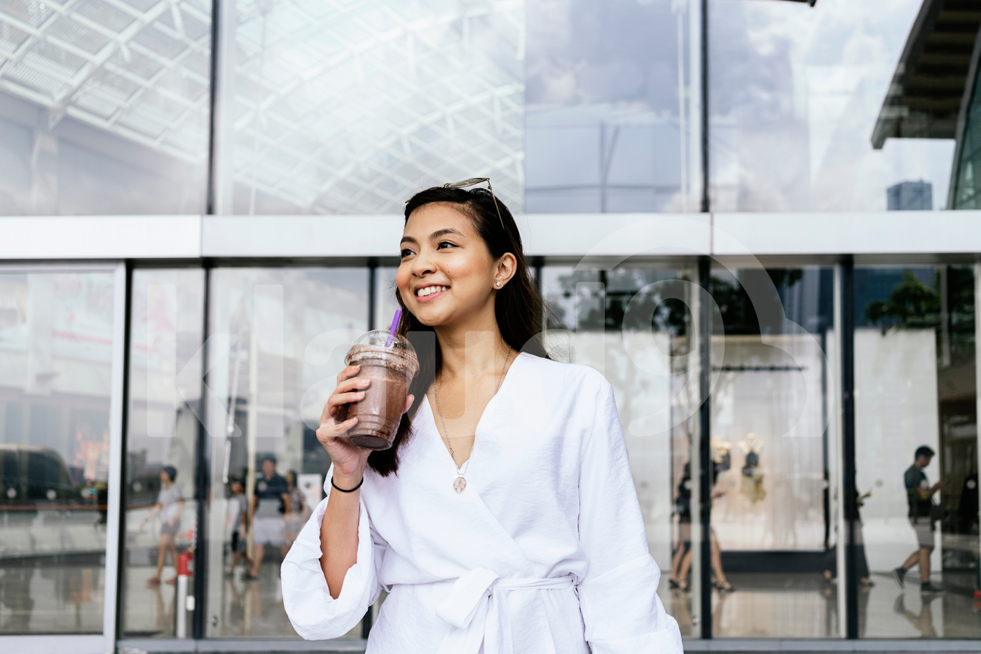 Young adult Asian woman standing in the mall holding a cup